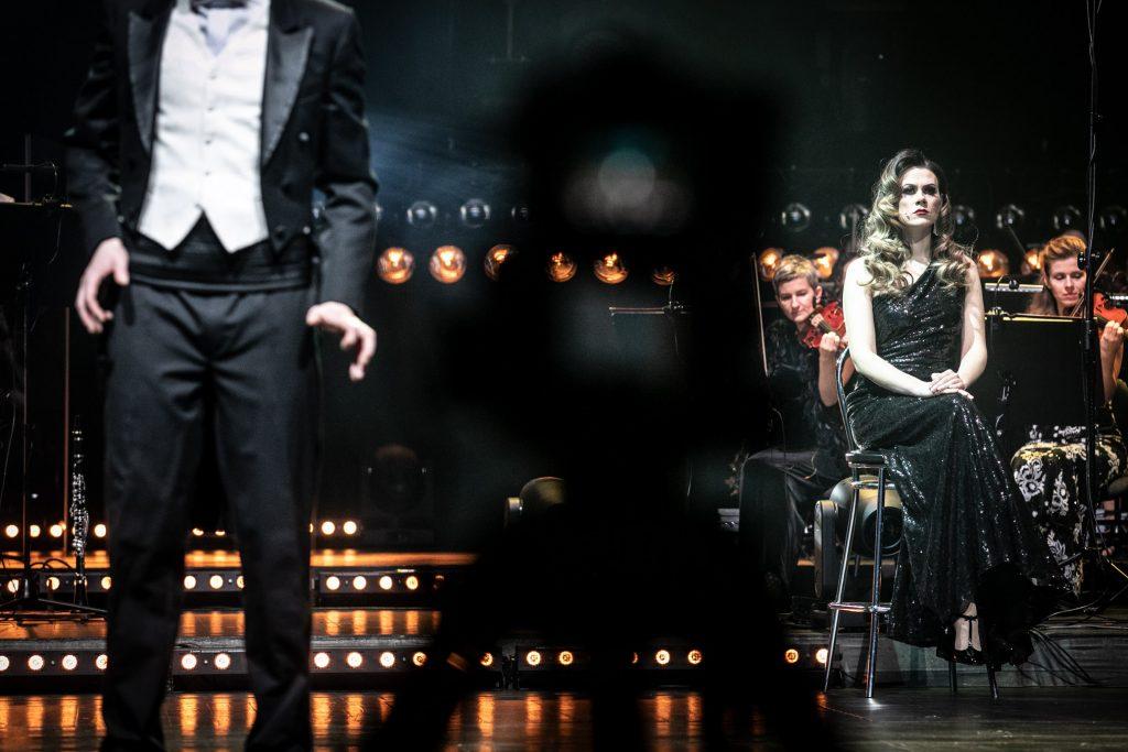 Po prawej stronie , na krześle siedzi kobieta w długiej sukni. Za nią część zespołu z sekcji smyczkowej. Po lewej stronie część sylwetki mężczyzny w czarnym fraku. Dalej widoczne podświetlone stopnie.
