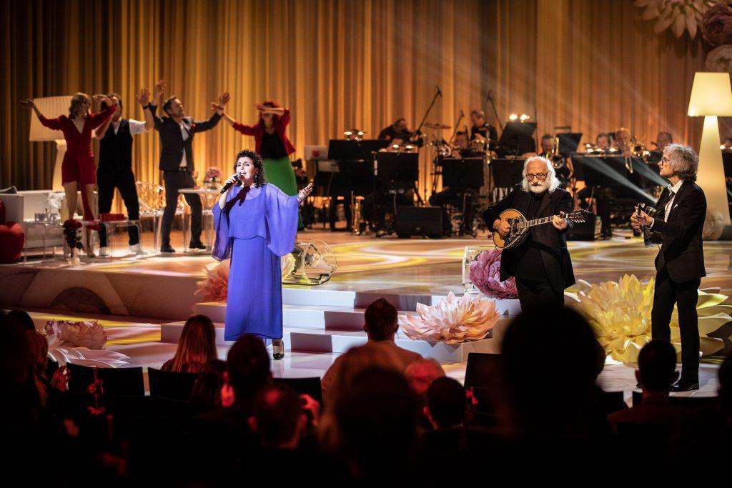Widok z końca widowni. Z przodu widoczna część publiczności siedząca tyłem. Na scenie w niebieskiej, długiej sukni artystka -Eleni. Po prawej stronie dwóch mężczyzn grających na mandolinach. Z tyłu widoczna część orkiestry. Po lewej stronie stoją dwie kobiety i dwóch mężczyzn. Wszyscy trzymają uniesione ręce do góry.