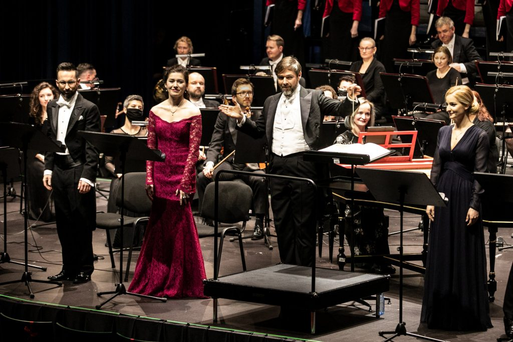 Koncert '' Stworzenie świata''. Zbliżenie na solistów i dyrygenta. Za nimi siedzi część orkiestry.