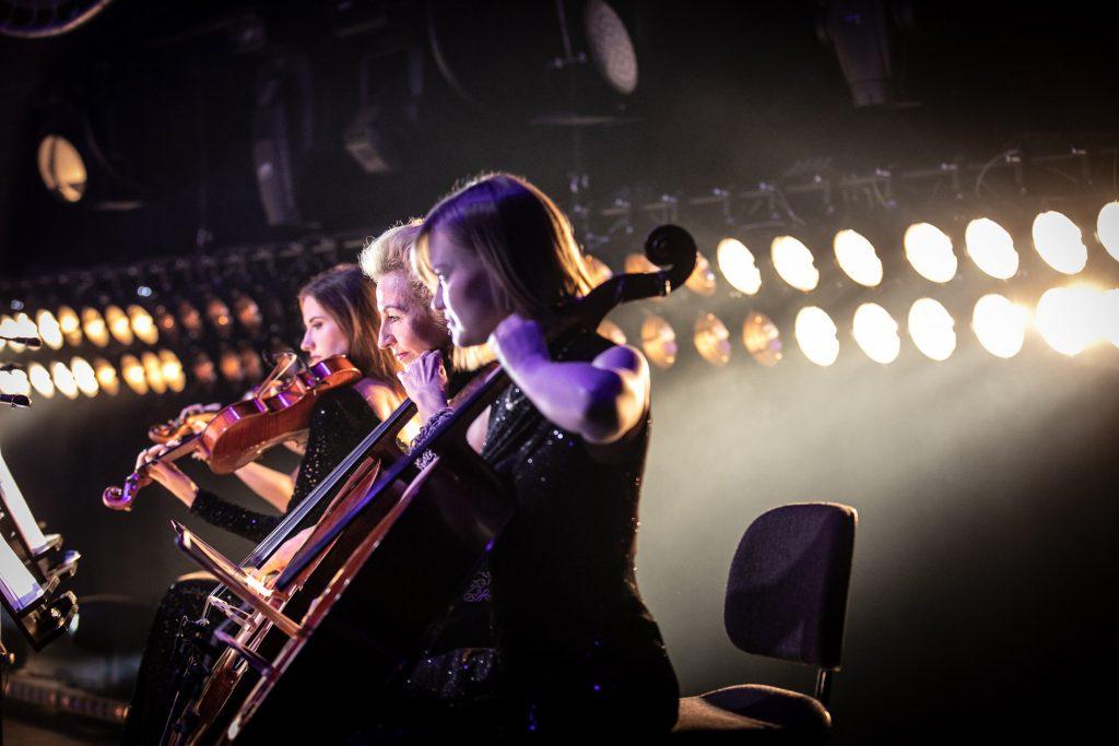 Na zdjęciu widoczne siedzące bokiem trzy kobiety grające na instrumentach smyczkowych. Za nimi, w dwóch rzędach świecące reflektory.