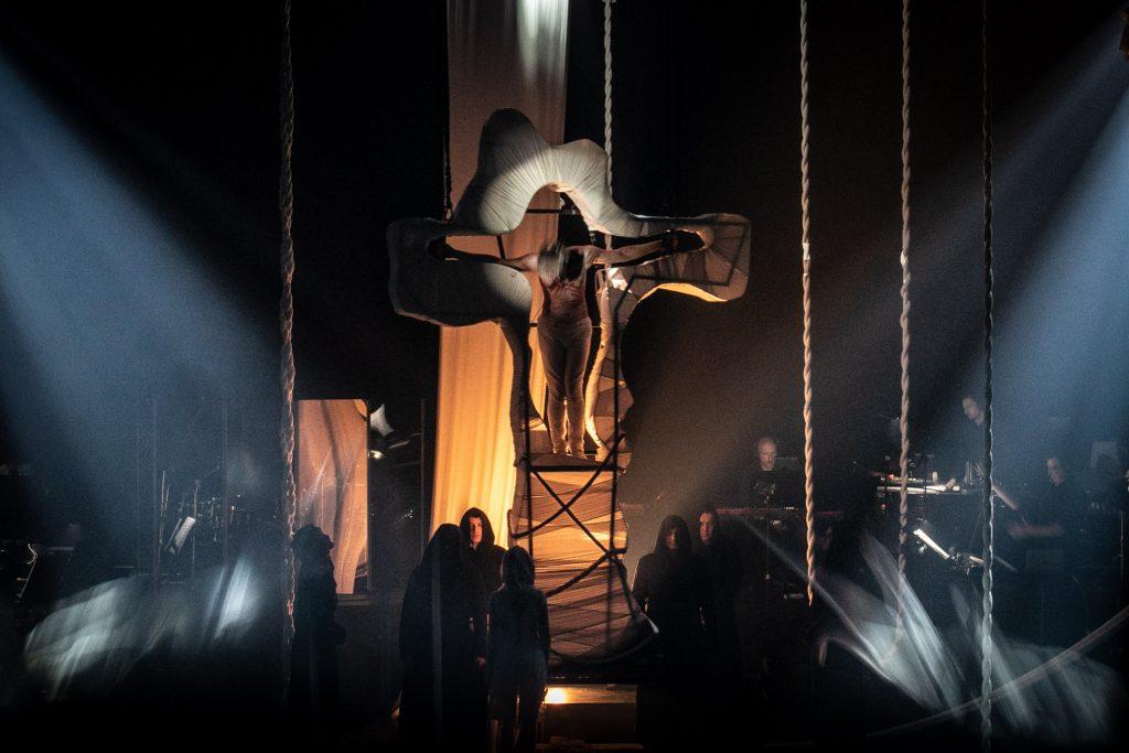Na środku wisi biały, duży krzyż. W nim stoi mężczyzna z głową opuszczoną w dół. Dookoła wiszą białe liny. Pod krzyżem stoi kilku mężczyzn w czarnych płaszczach z kapturami na głowach.
