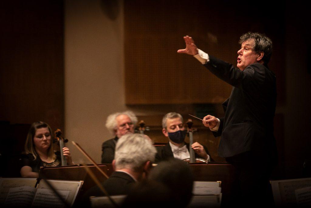 Dyrygent z ręką podniesioną w bok stoi przed orkiestrą.