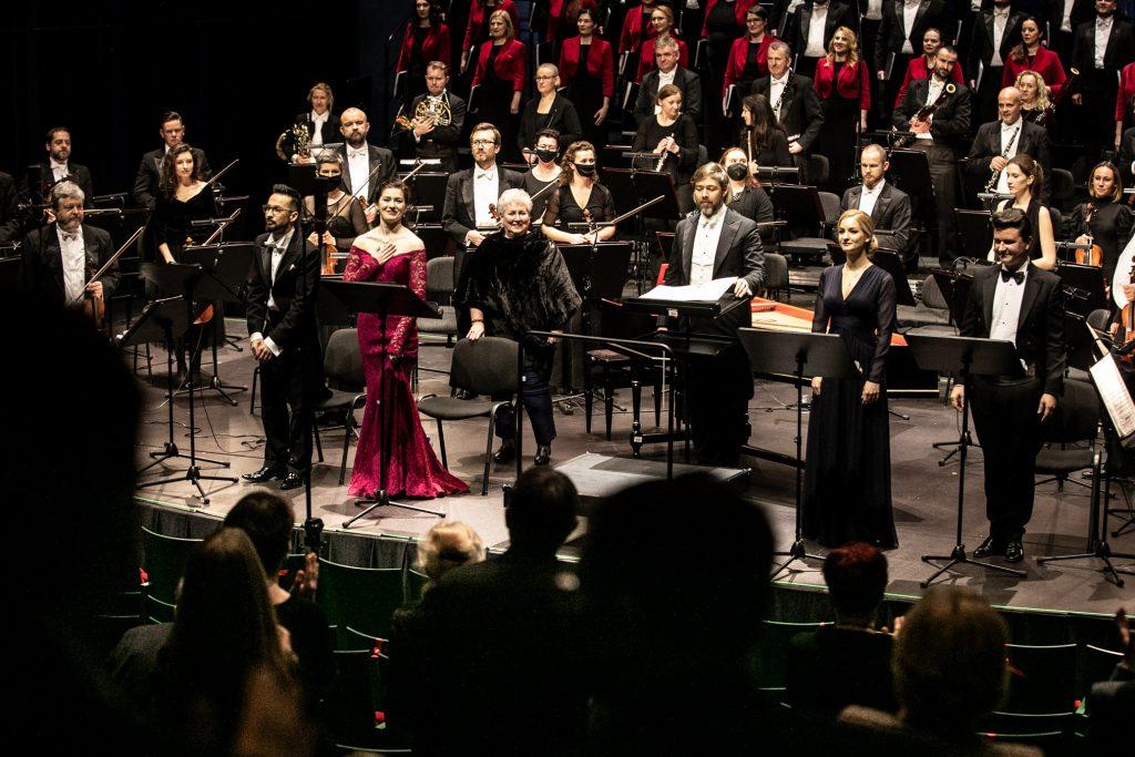 Koncert ''Stworzenie świata''. Na scenie Dyrektor Oifp Prof. Violetta Bielecka, dyrygent, soliści, Chór i Orkiestra Opery i Filharmonii Podlaskiej. Z przodu widoczna część widowni.