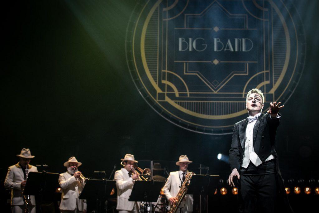 Na scenie po prawej stronie mężczyzna we fraku z wyciągniętą ręką do przodu. Na twarzy widoczne czarne smugi. Dalej czterech mężczyzn gra na instrumentach dętych. Na górze duża iluminacja z napisem ''Big Band''.