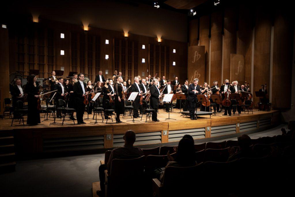 Publiczność oklaskuje orkiestrę stojąca na scenie wraz z dyrygentem.