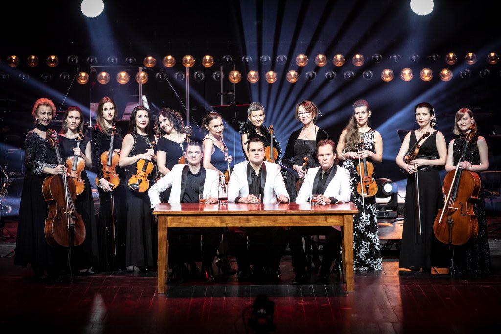 Na środku sceny stoi drewniany stół. Przy nim siedzi trzech mężczyzn w białych marynarkach. Za nimi, wzdłuż stoi częśc zespołu z sekcji smyczkowej. Nad nimi w dwóch rzędach widoczne reflektory.