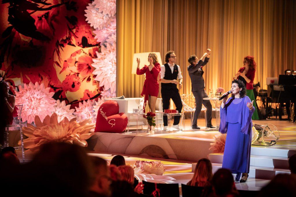 Na scenie w niebieskiej sukni z mikrofonem stoi artystka -Eleni. Za nią tańczą dwie kobiety i dwóch mężczyzn