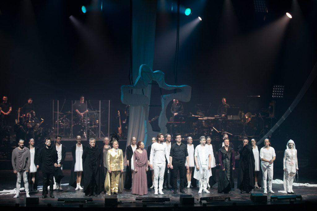 Na scenie stoją w rzędach wykonawcy musicalu ''Jesus Christ Superstar''. Za nimi z tyłu na podeście stoi orkiestra.