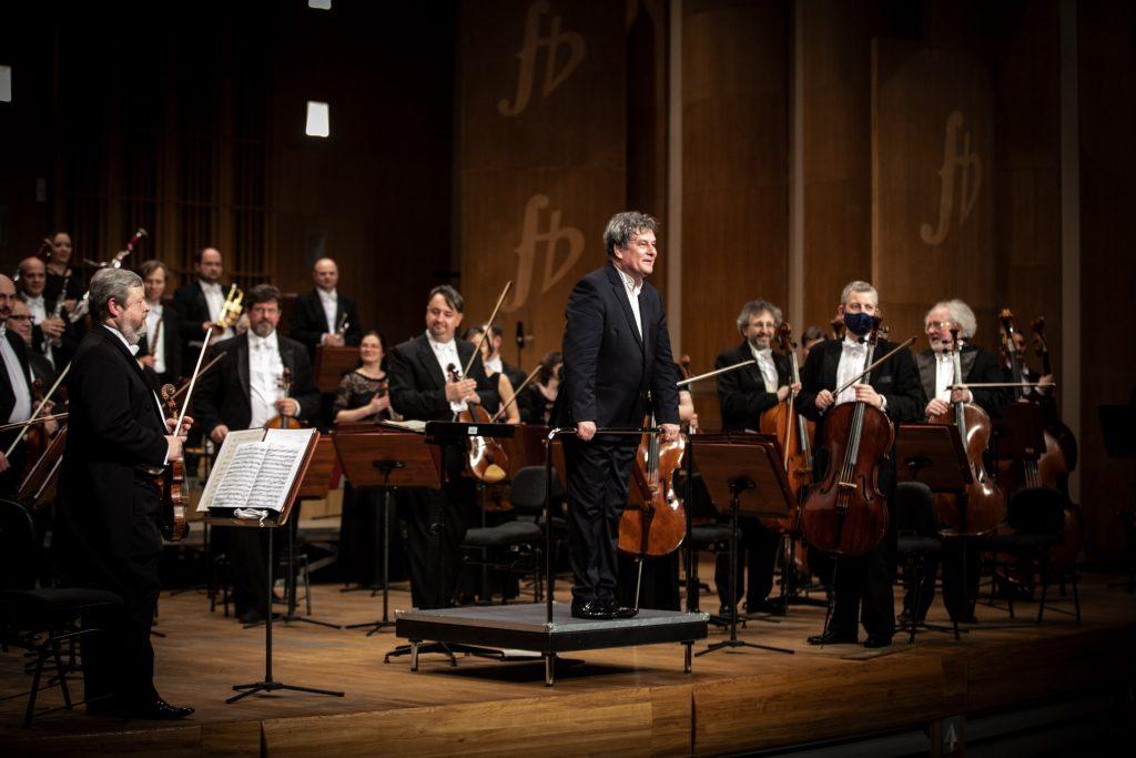 Przodem do widowni stoi dyrygent trzymając ręce na poręczy podestu. Za nim stoi orkiestra.