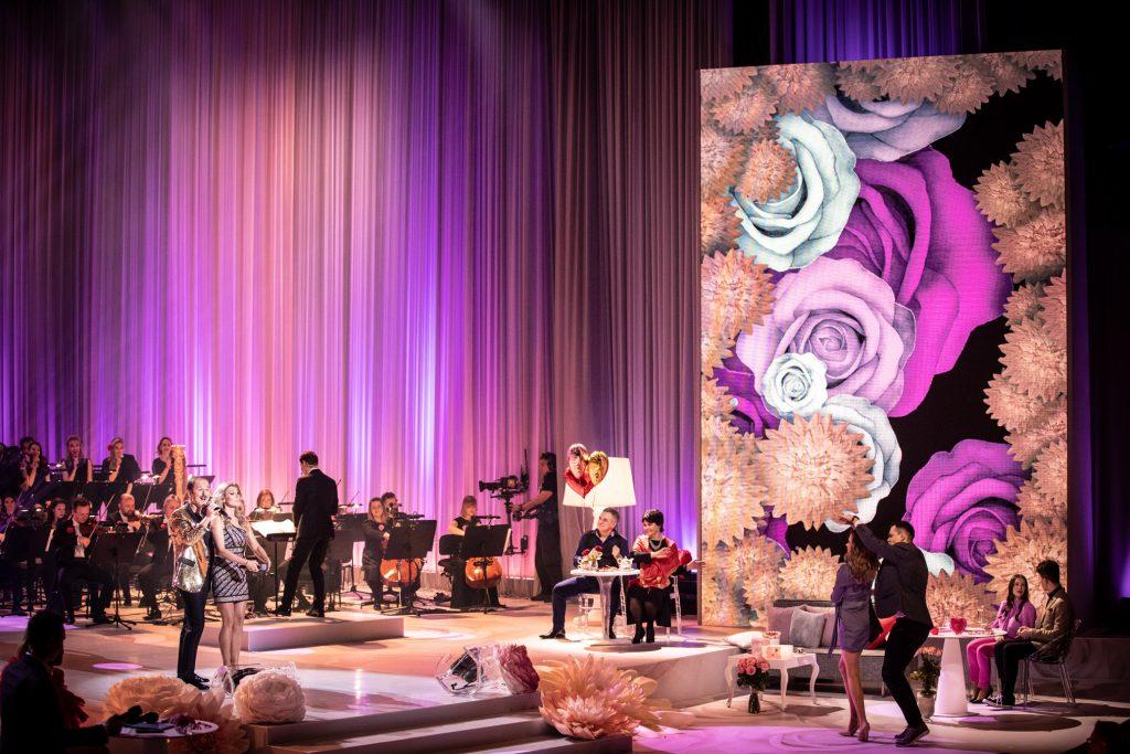 Po prawej stronie duży ekran na którym wyświetlone są kolorowe kwiaty. Przed nim przy stolikach siedzą pary. Na środku tańczy kobieta w szarej sukience i mężczyzna w garniturze. Po lewej stronie w złotej marynarce stoi mężczyzna, przed nim kobieta. Dalej siedzi orkiestra.