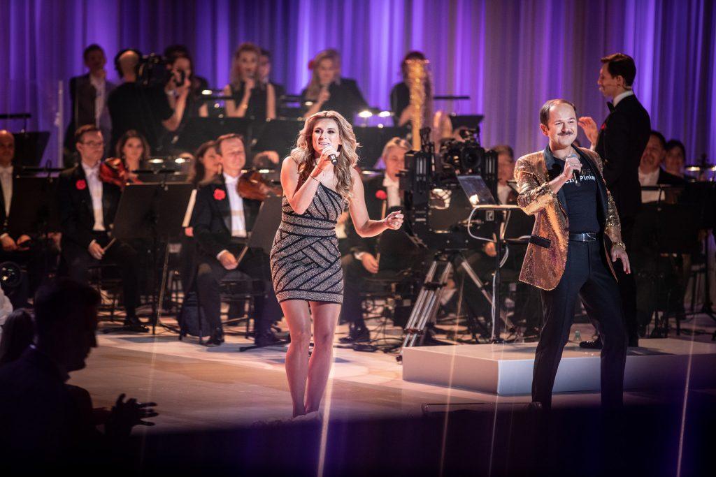 Na środku sceny stoi kobieta w srebrno-czarnej sukience i mężczyzna w złotej marynarce. Za nimi siedzi orkiestra.