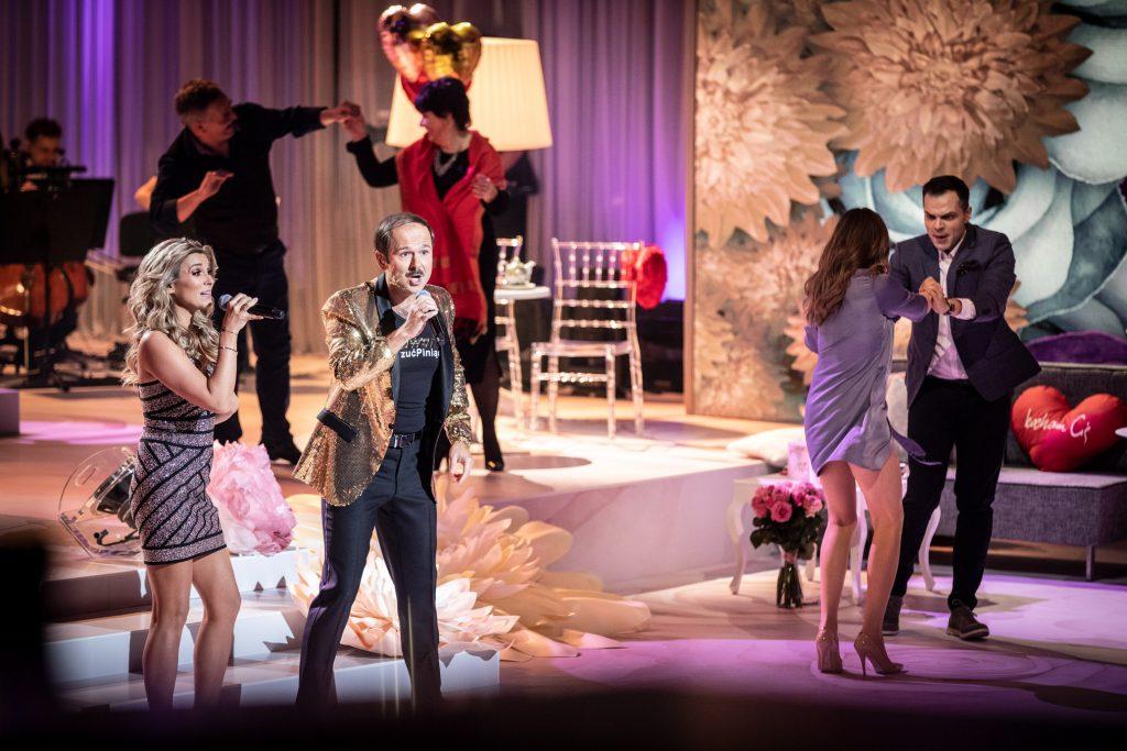 Na środku sceny z mikrofonami stoją kobieta w srebrnej sukience i mężczyzna w złotej marynarce. Po prawej stronie tańczy para trzymając się za ręce. Dalej na podeście tańczy inna para.
