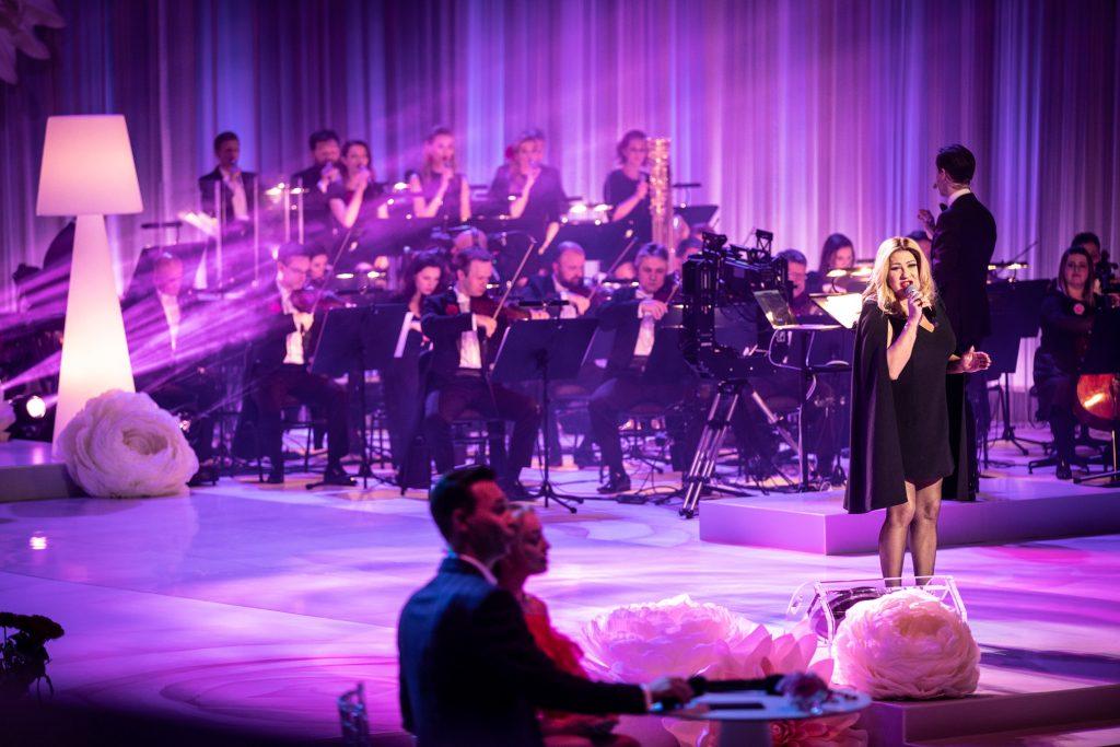 Na środku, przy stoliku siedzi kobieta w czerwonej sukience i mężczyzna w garniturze. Dalej w czarnej sukience stoi z mikrofonem kobieta. Za nią siedzi część orkiestry , przed nimi stoi dyrygent.