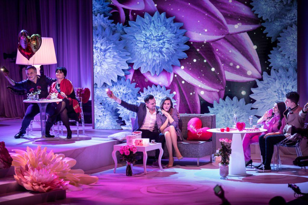 Na szarej sofie siedzi para, kobieta w niebieskiej sukience i mężczyzna w garniturze. Obok leży czerwona poduszka w kształcie serca. Za nimi na dużym tle widoczne kolorowe kwiaty. Po obydwu stronach , przy stolikach siedzą pary.