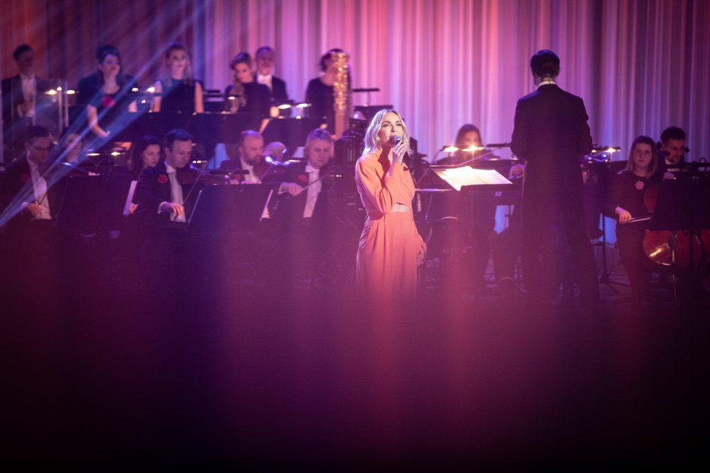 Na środku stoi kobieta z mikrofonem . Za nią siedzi orkiestra , przed nią dyrygent.