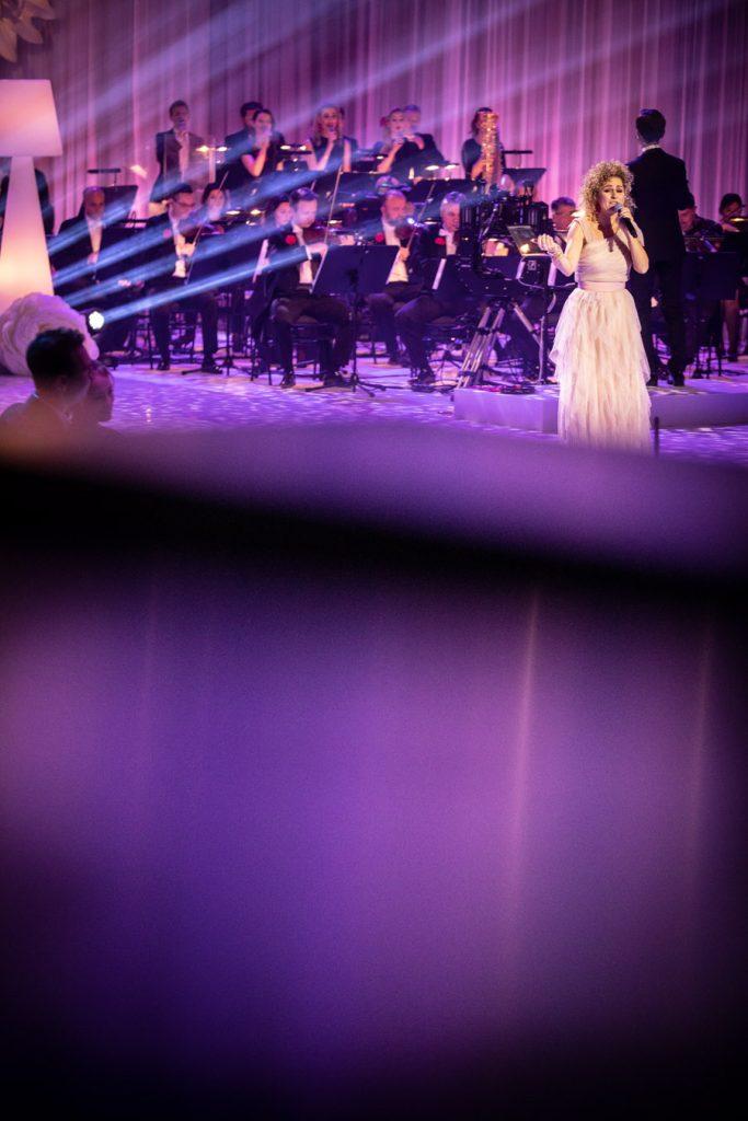 Na scenie stoi kobieta w jasnej sukni , w ręku trzyma mikrofon. Za nią siedzi orkiestra. Z lewej strony widoczne smugi światła.