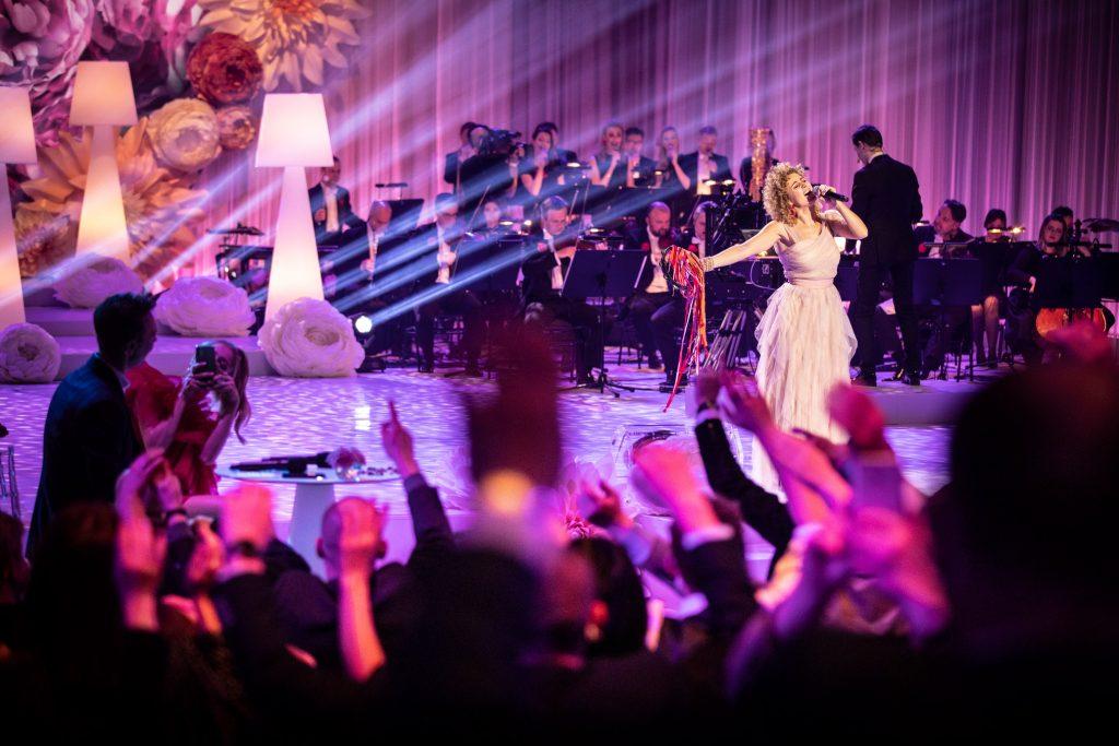 Na scenie stoi kobieta w jasnej sukni , w ręku trzyma mikrofon. Za nią siedzi orkiestra. Z lewej strony widoczne smugi światła. Po lewej stronie stoi kilka wysokich, białych lamp. Z przodu widać podniesione do góry ręce publiczności.