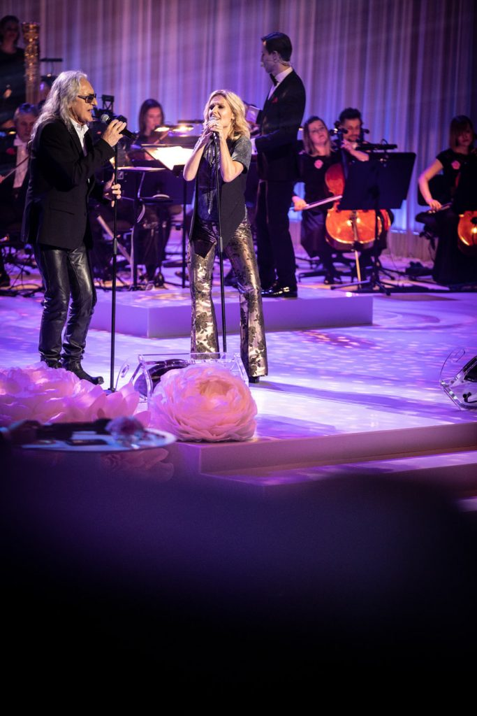 Na scenie, przy mikrofonach stoi para, kobieta w szerokich, złotych spodniach i mężczyzna w skórzanych spodniach i okularach przeciwsłonecznych. Przed nimi na scenie leżą duże , jasne róże. Za nimi widoczna część orkiestry.