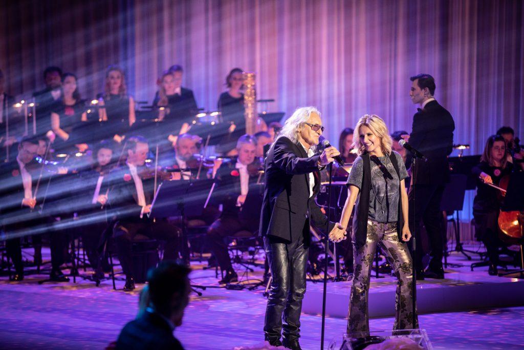 Na scenie, przy mikrofonach stoi para, kobieta w szerokich, złotych spodniach i mężczyzna w skórzanych spodniach i okularach przeciwsłonecznych. Trzymają się za ręce. Za nimi siedzi część orkiestry. Z lewej strony widoczne smugi jasnego światła.