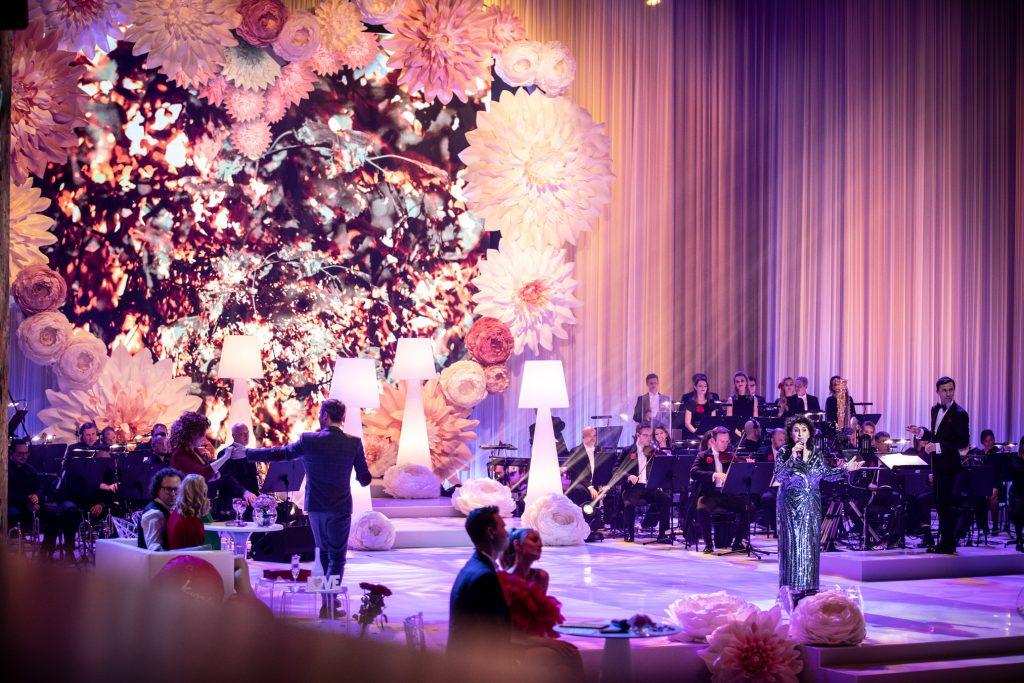 Na środku stoi kobieta w długiej, błyszczącej sukni. Za nią siedzi orkiestra. Z tyłu widoczne bardzo duże serce z kwiatów. Przed nim na stopniach stoją wysokie, białe lampy. Po lewej stronie przy stolikach siedzi kilka par.