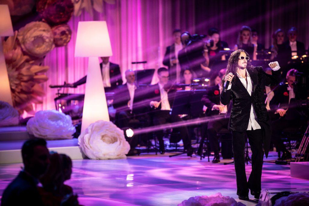 Na środku, w czarnych spodniach i marynarce stoi mężczyzna. W ręku trzyma mikrofon. Za nim widoczna część orkiestry. Obok stoi wysoka, biała lampa. Przy niej leży duża, biała róża.
