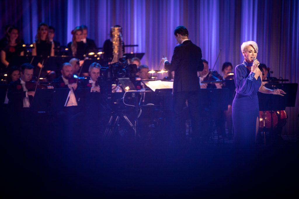 Po prawej stronie stoi kobieta w długiej , niebieskiej sukni. Z tyłu siedzi orkiestra.