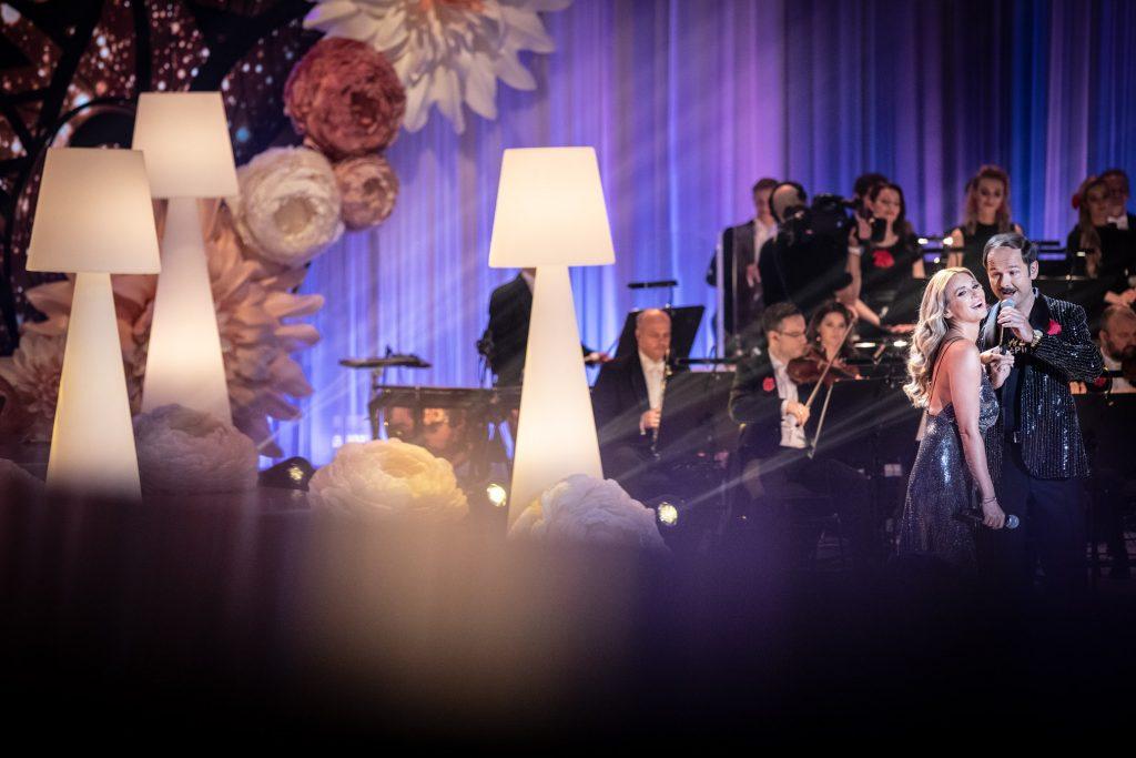 Po prawej stronie, blisko siebie stoi para. Kobieta w srebrnej sukience i mężczyzna w błyszczącej marynarce. Za nimi widoczna część orkiestry. Po lewej stronie stoją wysokie, białe lampy.