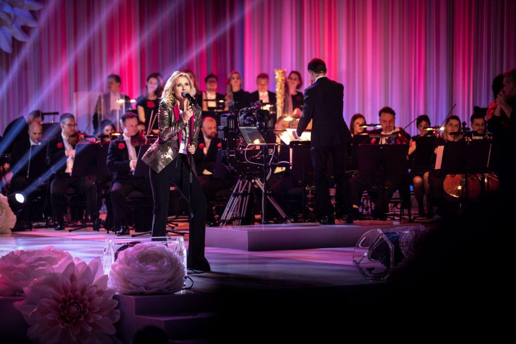 Na środku sceny przed mikrofonem stoi kobieta . Za nia siedzi orkiestra. Z przodu widoczne duże, jasne róże.