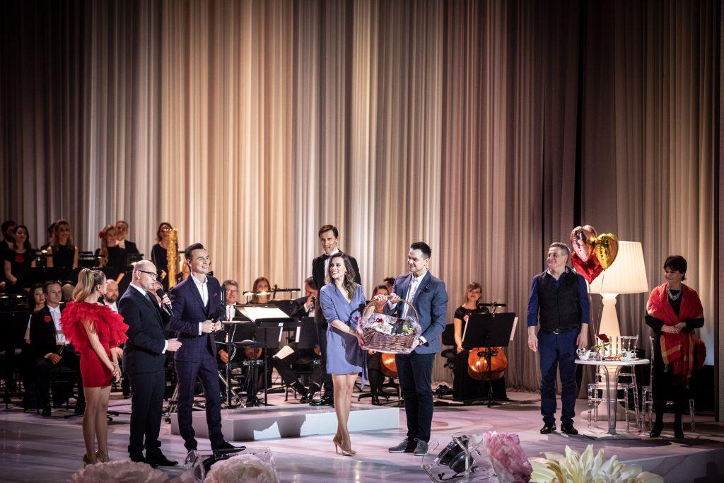 Na środku sceny stoi kobieta i mężczyzna trzymając prezentowy, duży kosz. Po lewej stronie stoi Marszałek Województwa Podlaskiego Pan Artur Kosicki z mikrofonem. Obok niego stoi kobieta w czerwonej sukience i mężczyzna w garniturze. Za nimi siedzi orkiestra.