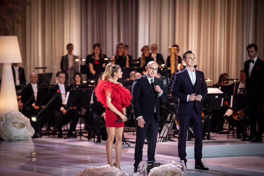 Na środku sceny stoi Marszałek Województwa Podlaskiego Pan Artur Kosicki. Obok niego stoi kobieta w czerwonej sukience i mężczyzna w garniturze. Za nimi widoczna część orkiestry.