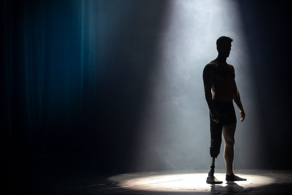 Na ciemnej scenie w białej smudze światła stoi mężczyzna z protezą nogi.