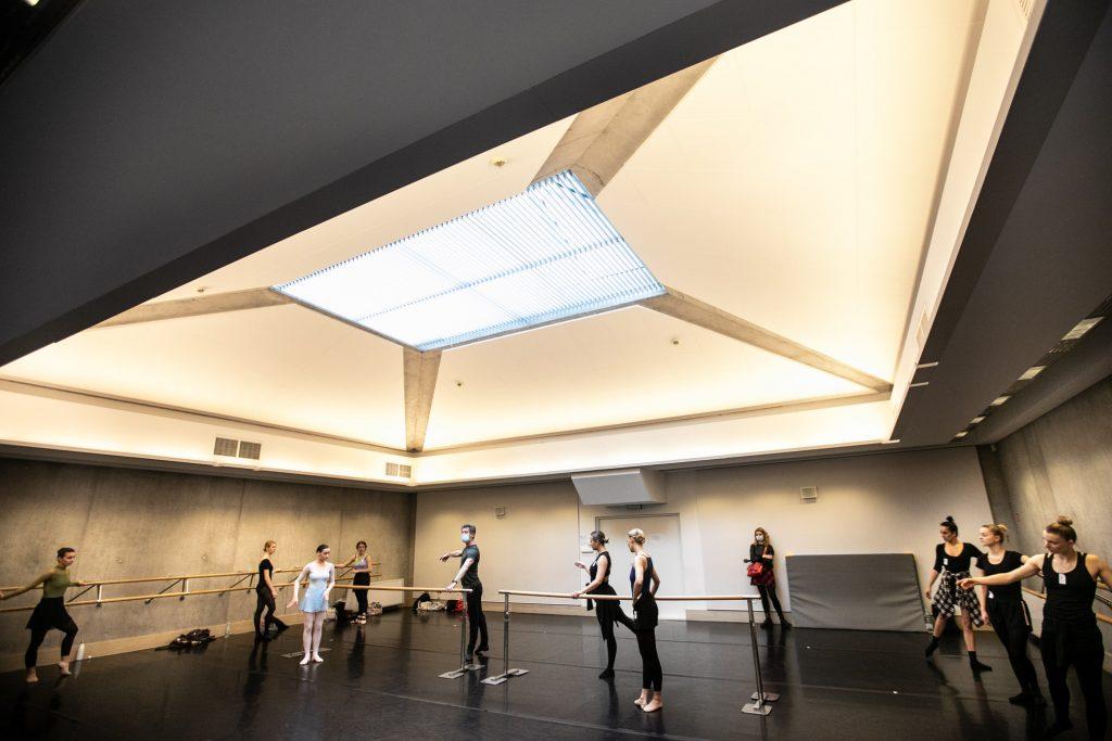 Na dużej sali przy drążkach baletowych stoi kilka osób.