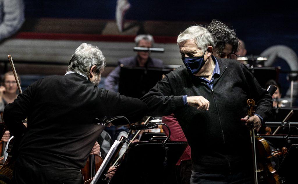 Dwóch mężczyzn dotyka się łokciami w geście powitania. Za nimi siedzi orkiestra.