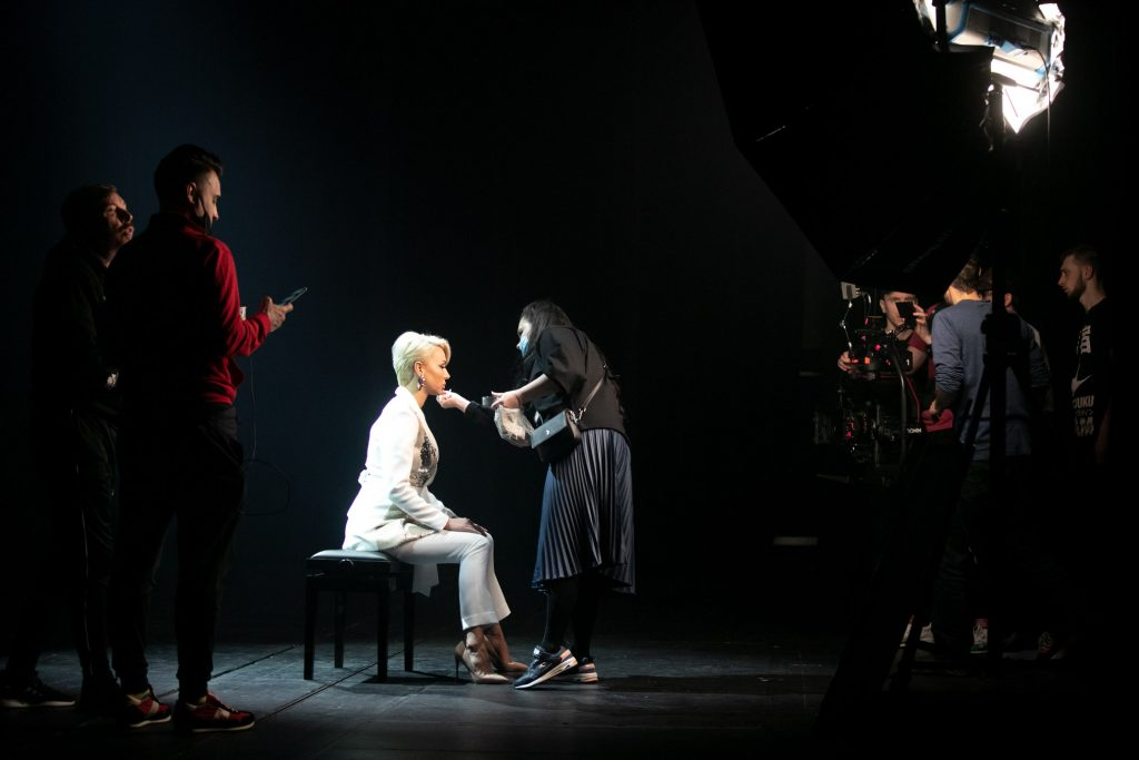 Na środku siedzi kobieta w białym garniturze. Przed nią stoi pochylona kobieta. Po prawej stronie stoi kilku mężczyzn za kamerą.