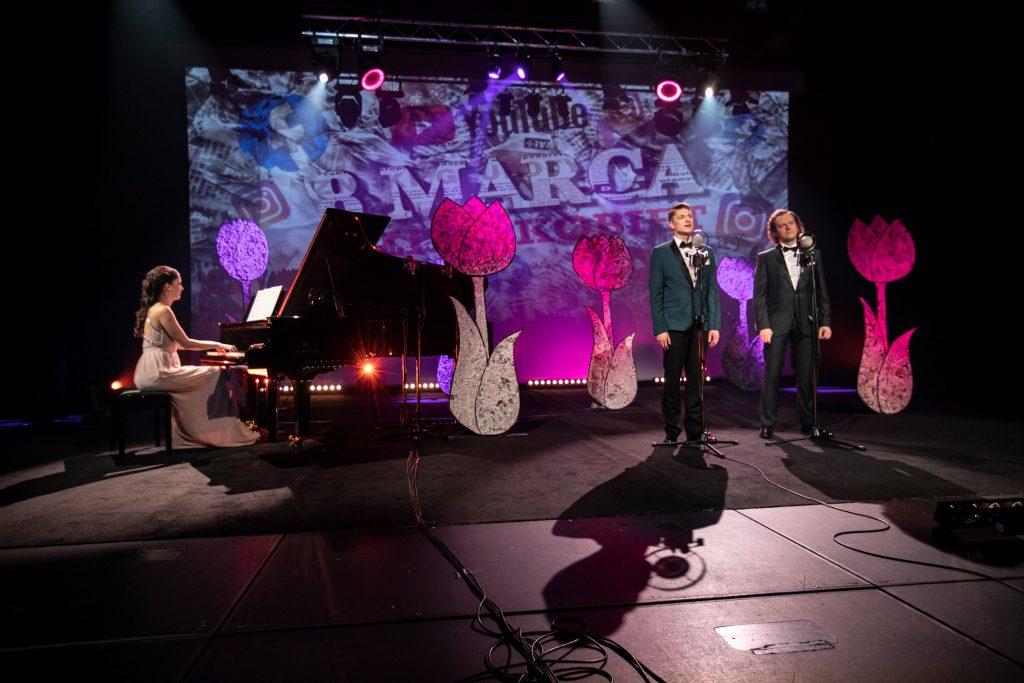 Dwóch mężczyzn w garniturach stoi przed mikrofonami. Po lewej stronie przy fortepianie siedzi kobieta w długiej sukni. Z tyłu wyświetla się iluminacja świetlna z napisem ''8 MARCA''.