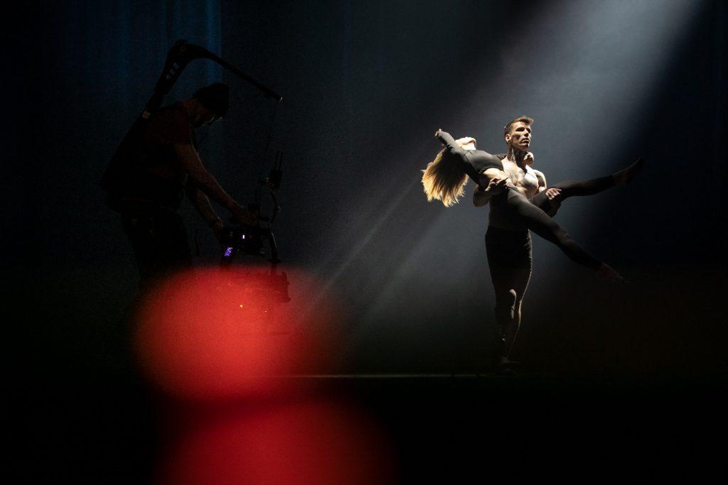 Mężczyzna z protezą nogi trzyma na rękach kobietę w pozycji tanecznej. Po lewej stronie stoi mężczyzna z kamerą.