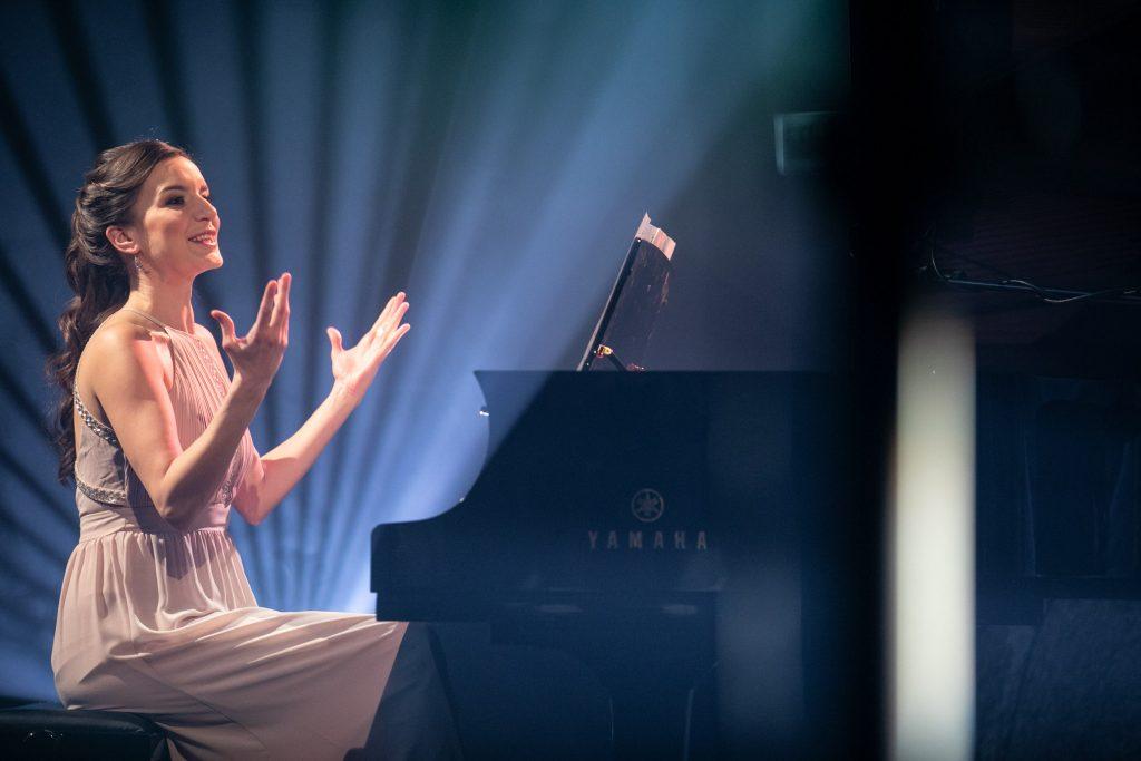Kobieta z uniesionymi rękoma siedzi przy fortepianie. Za nią widoczne smugi jasnego światła.