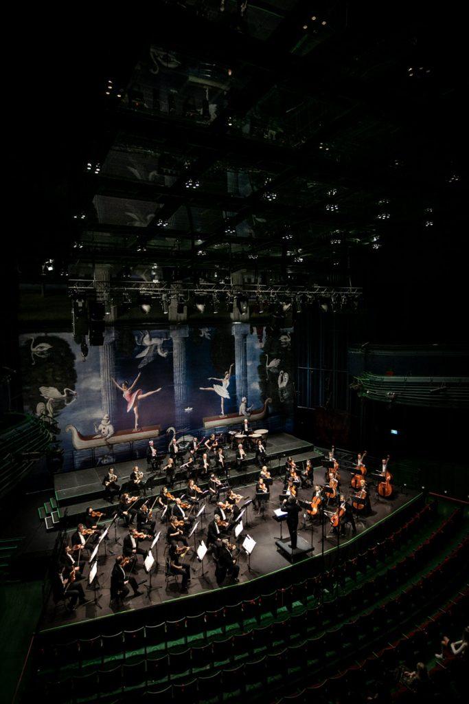 Widok z góry. Na scenie orkiestra wraz z dyrygentem podczas koncertu.
