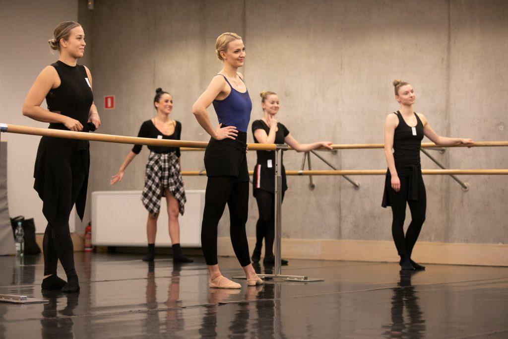 Przy drążkach baletowych stoi kilka kobiet patrząc w jednym kierunku.