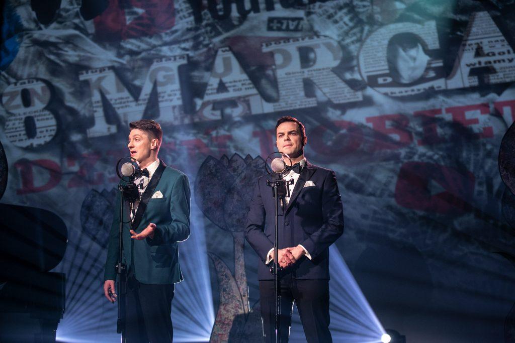 Dwóch mężczyzn stoi przed mikrofonami. Za nimi iluminacja świetlna z napisem ''8 MARCA''.