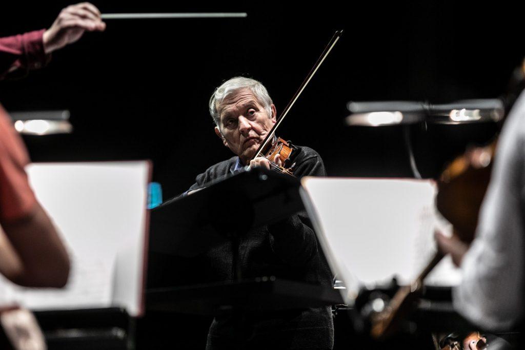Zbliżenie na solistę grającego na skrzypcach podczas próby do koncertu.