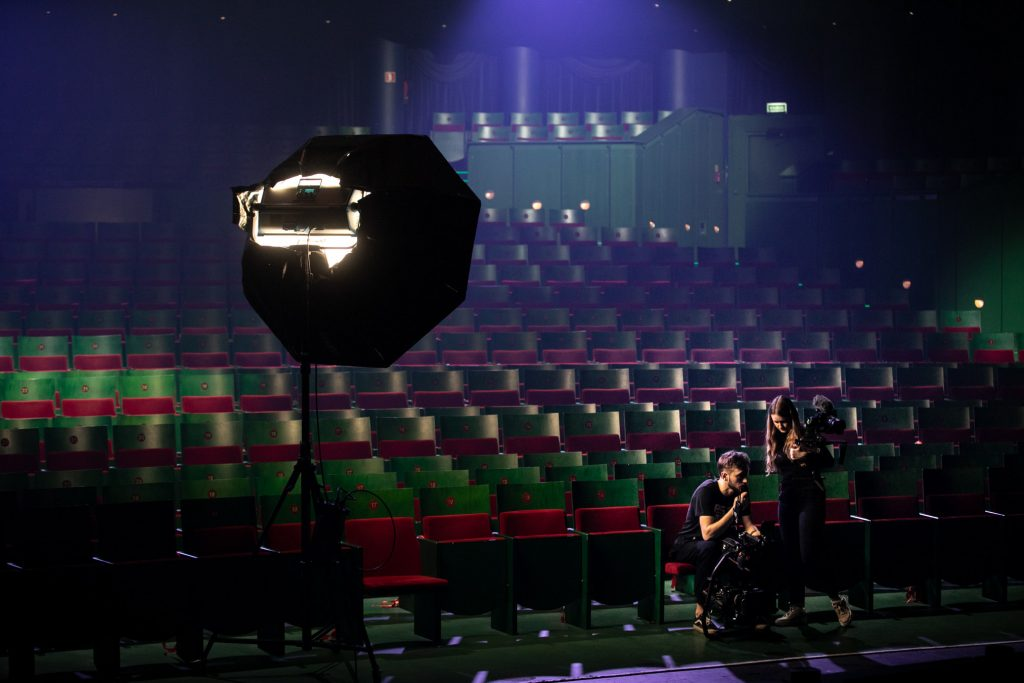 Widok na pustą widownię. Po lewej stronie stoi parasol zdjęciowy. W pierwszym rzędzie siedzi mężczyzna z kamerą. Obok niego stoi kobieta z aparatem.