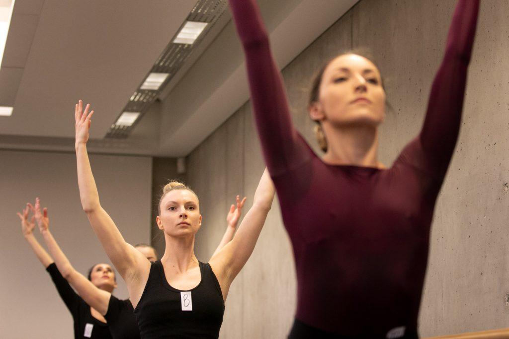 Kilka kobiet stoi w rzędzie za sobą trzymając ręce skierowane do góry.