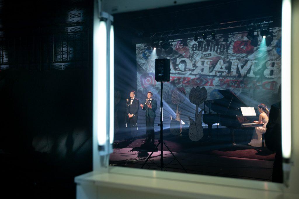 W lustrze toaletki odbija się widok ze sceny: dwóch mężczyzn stoi przed mikrofonami. Obok przy fortepianie siedzi kobieta w długiej sukni. Za nimi iluminacja świetlna z odwrotnym napisem ''8 MARCA''.