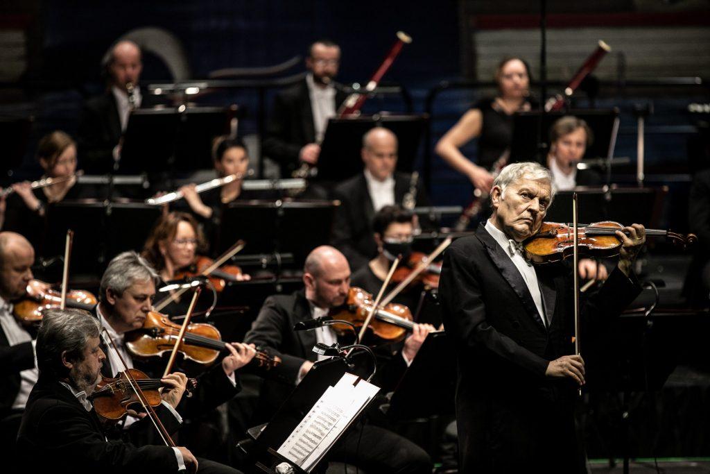 Na środku stoi solista podczas wykonywania utworu. Za nim gra orkiestra.