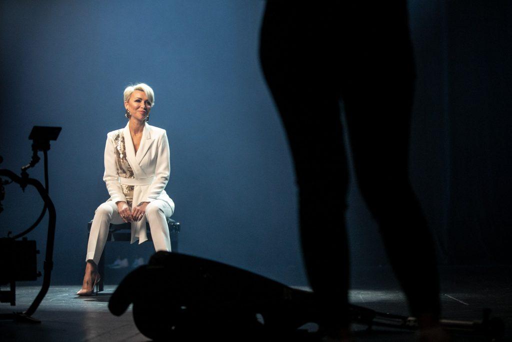 Na środku siedzi kobieta w białym garniturze. Na twarzy ma lekki uśmiech. Z przodu widoczna sylwetka tyłem