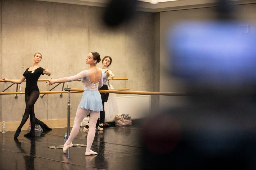 Trzy kobiety stoją przy drążkach w pozycji baletowej.