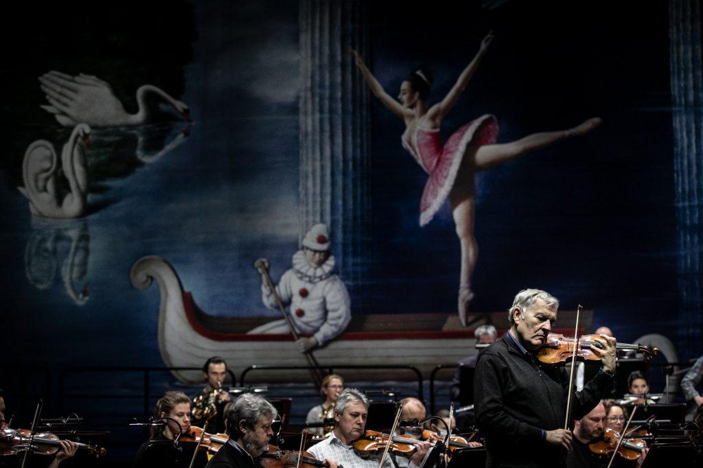 Zbliżenie na solistę podczas wykonywania utworu. Za nim siedzi orkiestra.