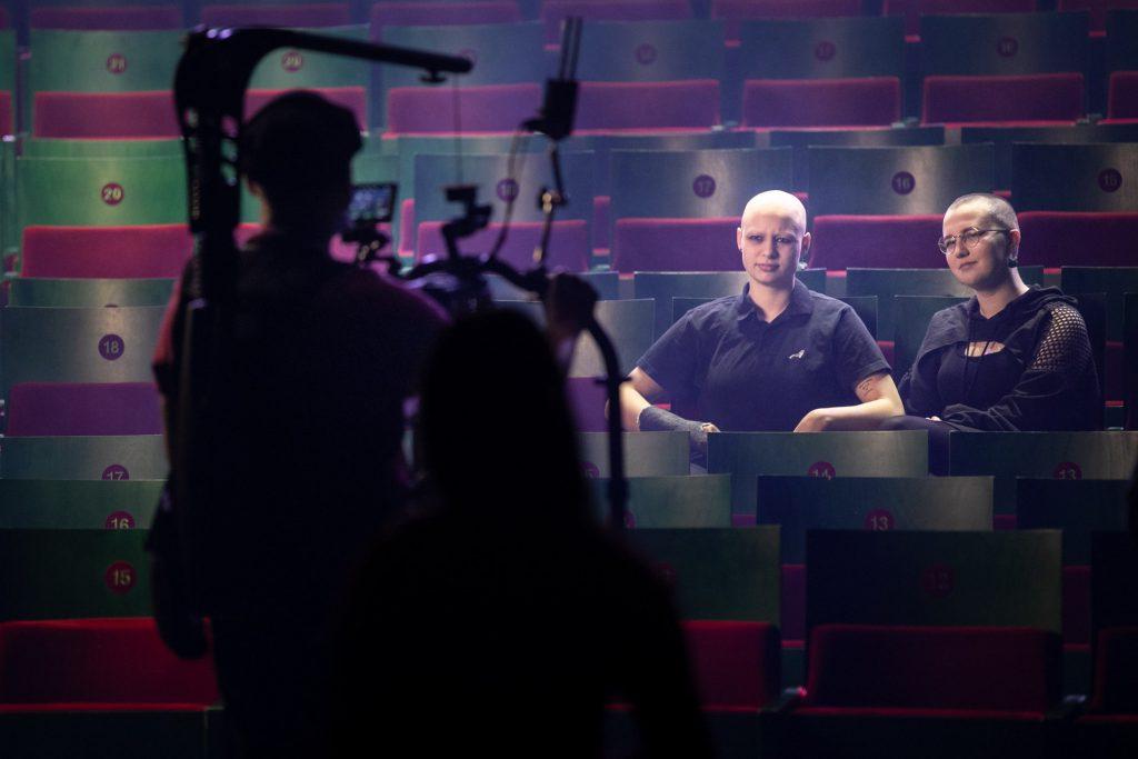 Na widowni siedzą dwie kobiety z obciętymi włosami. Patrzą w stronę kamery która znajduje się przed nimi.