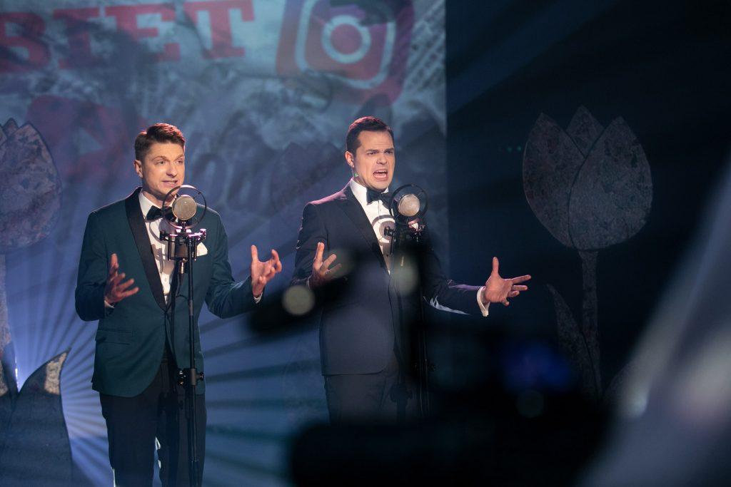 Dwóch mężczyzn w garniturach stoi przed mikrofonami na statywach. Ręce mają uniesione lekko do boków. Za nimi część iluminacji świetlnej z koncertu ''8MARCA''.